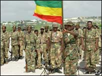 Ethiopian troops stand to attention as they hold an Ethiopian flag during a ceremony at the Mogadishu airport as they prepare to withdraw from Somalia