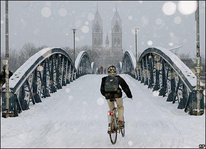 A cyclist crosses a snow-covered bridge in Freiburg