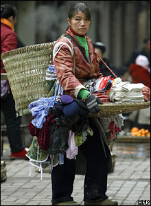 A heavily-laden street peddler waits for customers