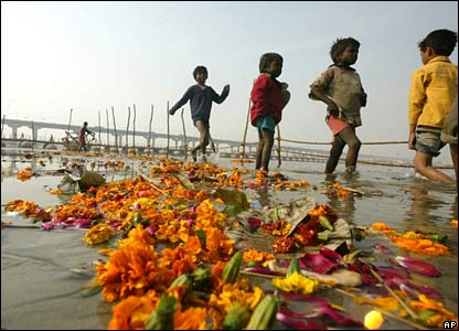 Indian children search for coins in the flower-strewn River Ganges