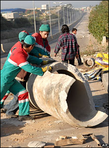 Street sweepers remove a concrete tube from a road in the Lebanese capital, Beirut