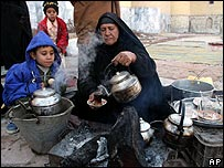 Displaced Iraqis make tea in a shelter north of Baghdad