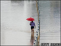 A man walks along a flooded road in Nanjing, Jiangsu Province (9 July 2007)