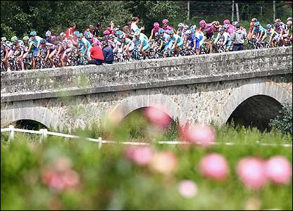 The peloton crosses a bridge