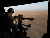 A US marine fires a machine gun from a helicopter over Anbar province, Iraq