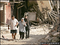 Lebanese civilians walk among bomb damage in Beirut, August 2006