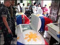 Philippine marines look at the coffins of their dead colleagues