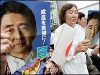 Supporters of the ruling Liberal Democratic party hold leaflets with photos of Prime Minister Shinzo Abe