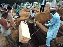 Gravediggers bury coffins in Islamabad, 12 July 2007