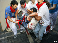 Revellers carry a runner gored by a bull during the San Fermin festival in Pamplona