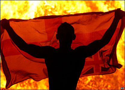 A Protestant youth watches a bonfire on the Shankill Road area of West Belfast, Northern Ireland early on 12 July