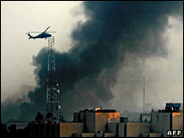 A US helicopter hovers over smoke caused by a car bomb in Baghdad