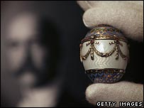 One of the lots: a Faberge enamel and gold egg with a portrait of King George in the background