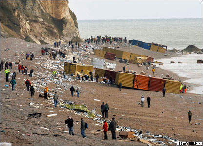 People rummage through containers on Branscombe beach, Devon