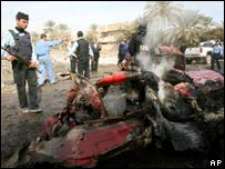 Iraqi police check the smouldering wreck of a taxi hit by a bomb blast in Baghdad