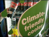 """Botellas de Coca Cola y un anuncio sobre un refrigerador """"verde""""."""