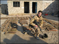 Soldier posing by captured ammunition (Source: MoD)