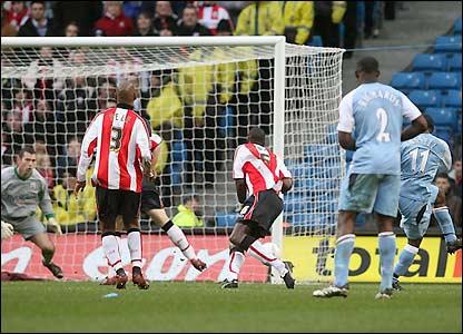 Vassell drives the ball towards goal