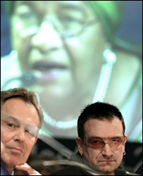 Tony Blair and Bono in front of a screen showing Liberian president Ellen Johnson Sirleaf