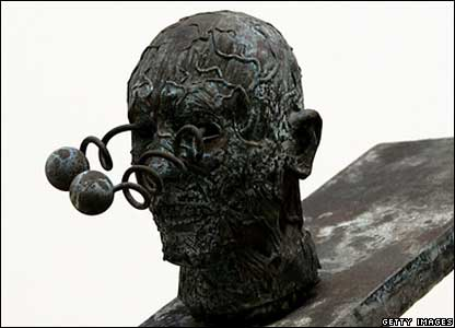 A statue of a man's head with eyeballs on springs