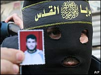 A Palestinian militant of Islamic Jihad holds a photo of Mohammad Siksik