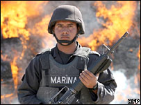 A Mexican soldier stands in front of marijuana being incinerated