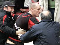 Gareth Thomas is restrained by Toulouse assistant coach Serge Lairle (left)