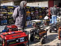 n Iraqi passes by stacks of generators in a marketplace in Baghdad, Iraq