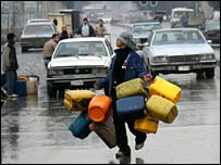 A man makes his way to queue for heating oil in Baghdad