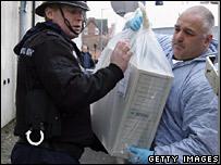 Policeman and forensics officer handling hardware