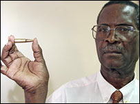 Zimbabwean newspaper editor Bill Saidi holds up a bullet sent to him