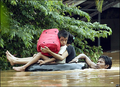 A man pushes children in a raft during floods in Indonesia
