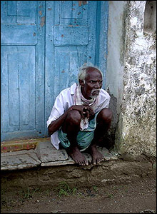 An old man sitting on a doorstep