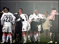 Palermo players try to get away from the tear gas during their game with Catania