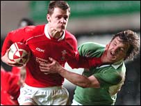 Wales' Lewis James holds off the Ireland defence