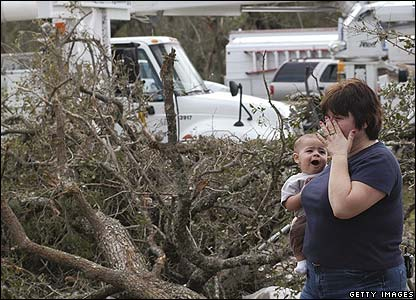 A woman holds her grandchild as she looks at the wreckage of her home