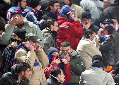 Catania fans cover their faces to protect themselves from smoke and tear gas