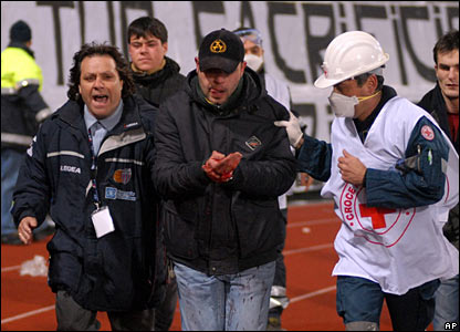 An injured fan with a bleeding hand is helped by a medic