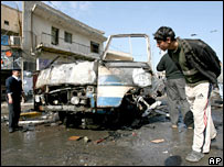 Man examines wreckage of bombed minibus in mainly Shia Karrada district of Baghdad