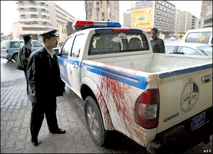 An Iraqi policeman inspects the back of his vehicle after evacuating wounded people from the site of the Baghdad bombing, 3 February 2007.