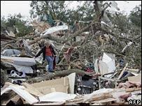 A woman walks through debris of a mobile home in Lady Lake, Florida