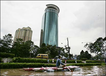 An Indonesian man paddles down a flooded road in central Jakarta