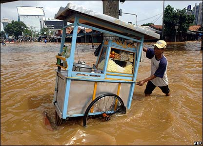 A food vendor pushes his cart through the Jakarta streets