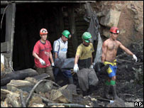 Rescuers carry the body of a dead miner