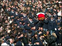 Crowds watch as policemen carry the coffin of the policeman Filippo Raciti