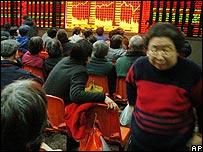 Inversores chinos siguen la evoluci�n de los precios de las acciones en los monitores digitales del mercado en Shanghai, China