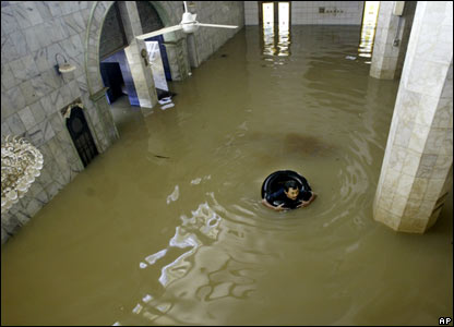 An Indonesian man floats in a tube in a flooded mosque in Jakarta