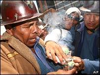 Miners lighting sticks of dynamite