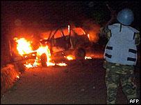 UN peacekeeper looks at burning car