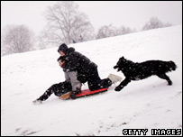 Two children sledging on Hampstead heath, London